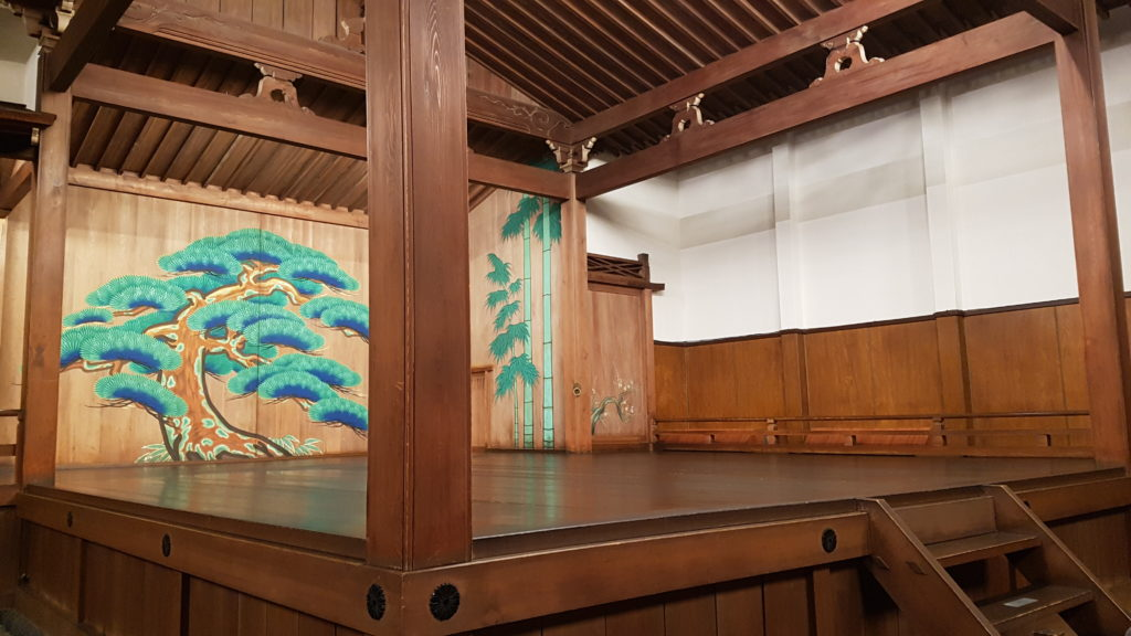 A small set of wooden stairs descend from the front of the noh stage