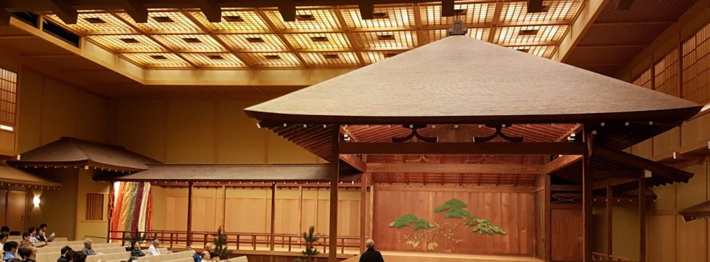 A simple roof sits over a nogaku stage under the ceiling lights of the larger building in which the whole stage is enclosed