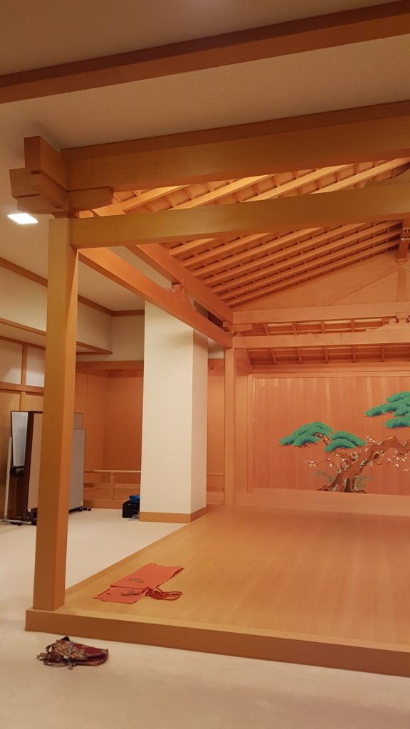 A slightly raised noh stage, complete with pillars, roof, and mirror board, on a carpeted floor