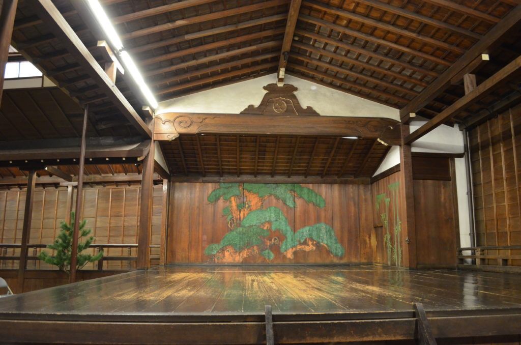 An old wooden noh stage with light patches on the surface where the varnish has been worn thin