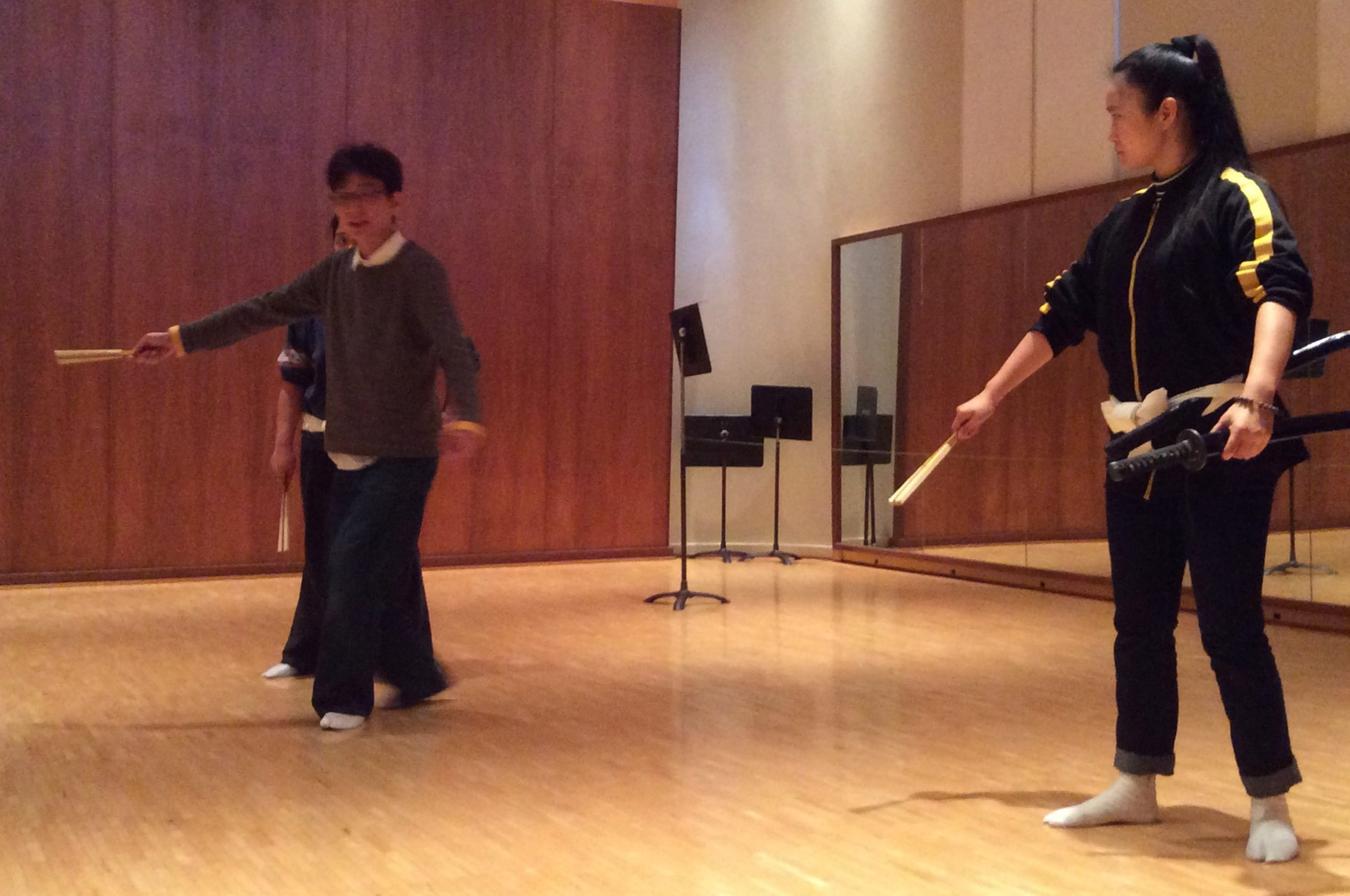 Shigeyama Sennojō III teaches two UHM students, all with a fan in their right hand