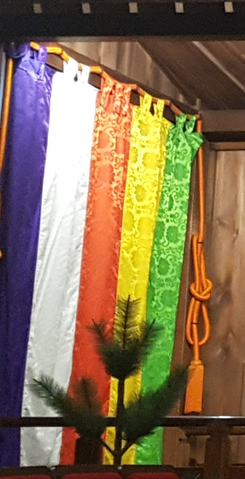 A silk curtain with purple, white, red, yellow, and green vertical stripes with red ropes tied in ornate knots on either side