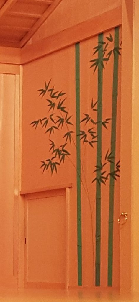 A small square door take located on the bottom left corner of a narrow wooden panel with green bamboo painted on it