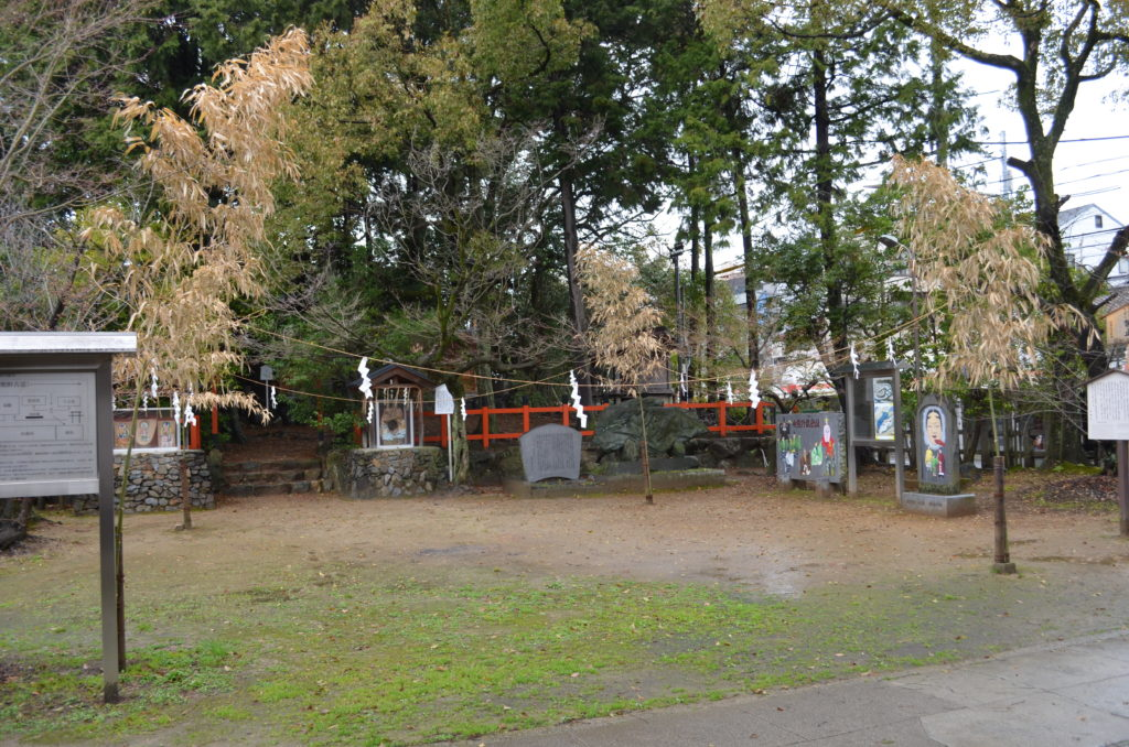 An information sign, stone monuments and trees occupy the perimeter of an open square at Imagumano Shrine