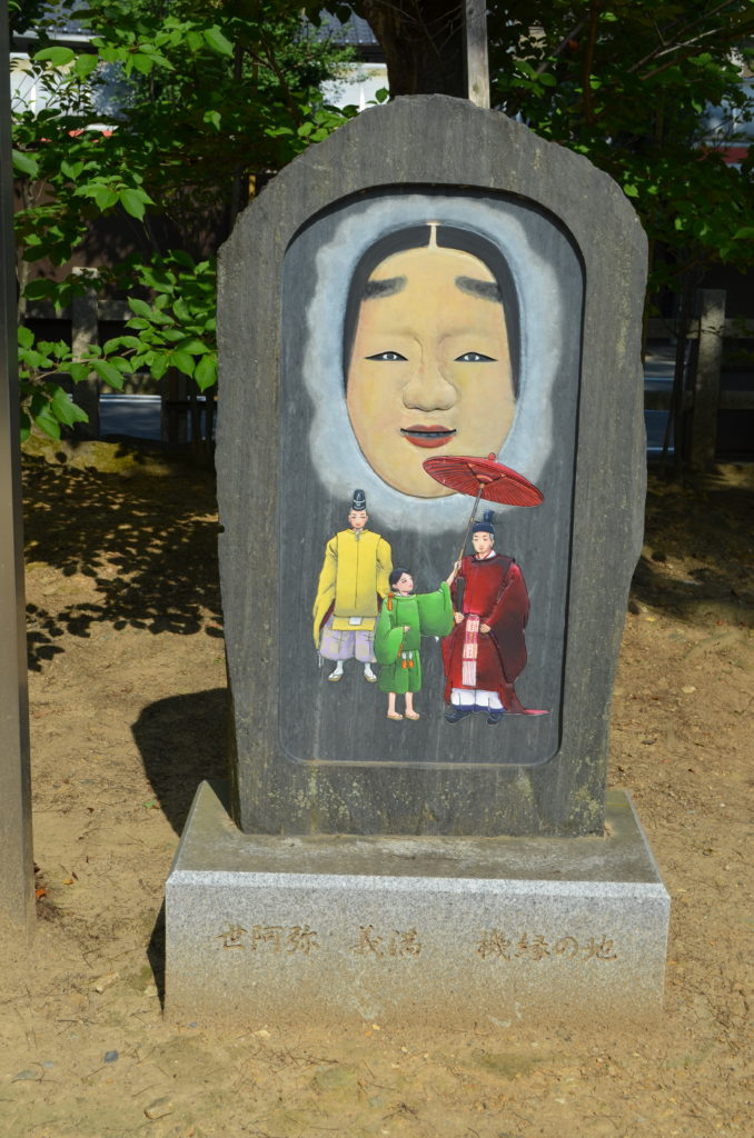 A rounded stone monument with a picture of a noh mask and three figures in traditional Japanese dress