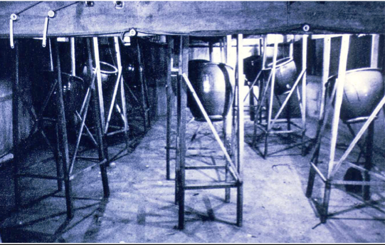 Clay jars are mounted in wooden braces under a wooden noh stage