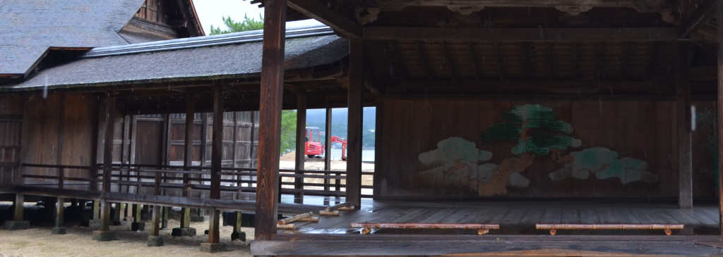 The bridgeway and stage of a weathered, wooden noh stage at Itsukushima Shrine.