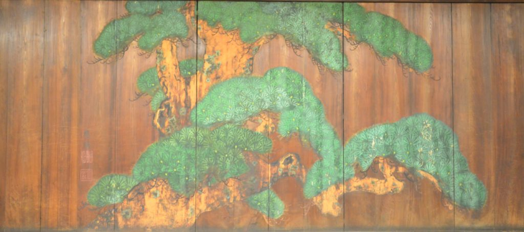 Faded painting of a pine tree on a wooden panel