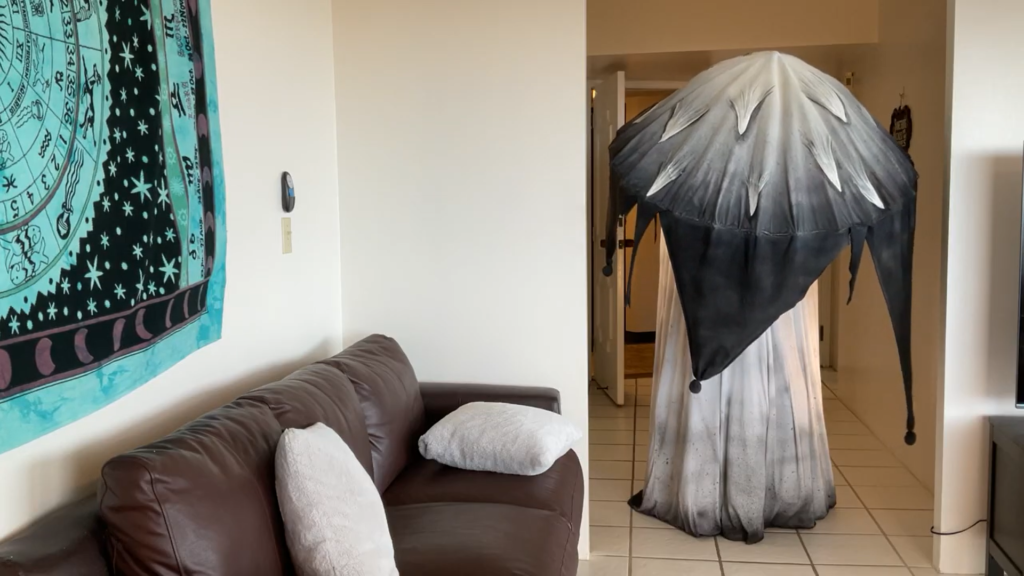 A person in a giant mushroom costume stands down a hallway at the threshold of a living room