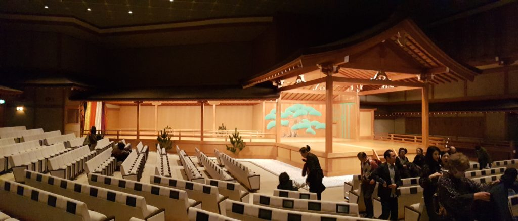 Audience seats at along the front and side of the nogaku stage with small screens for title viewing.