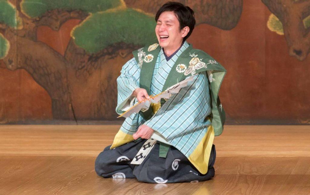 Shigeyama Sennojō III kneels on a traditional wooden stage in kyōgen costume laughing and holding an open fan