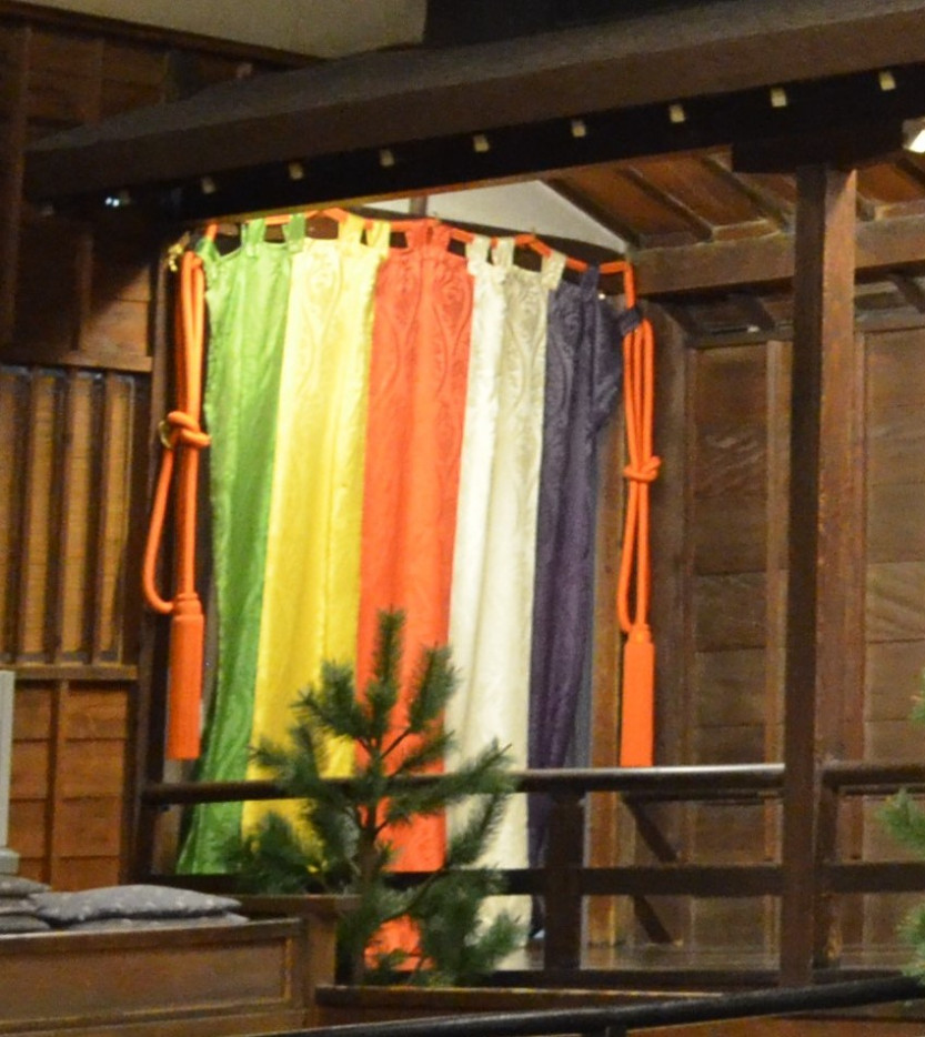 A silk curtain with green, yellow, red, white, and purple vertical lines of colour and red ropes tied in a knot on either side
