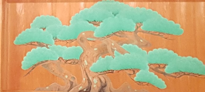 A large painted pine tree that stretches across the entirely of a wooden panel.