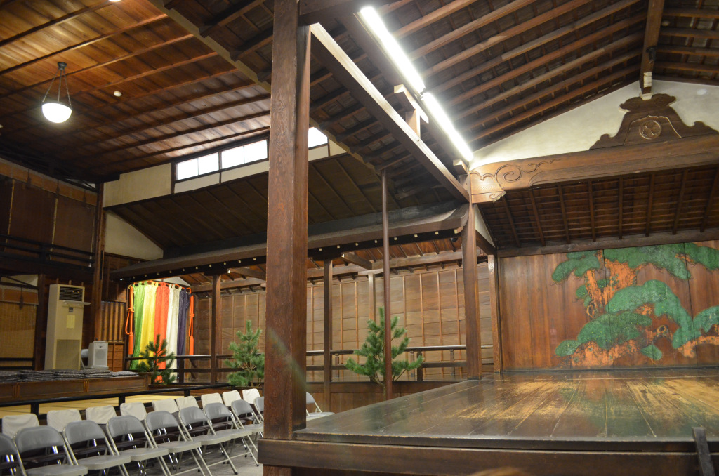 Side seating of a nogaku stage comprised of tatami terraces and metal folding chairs.