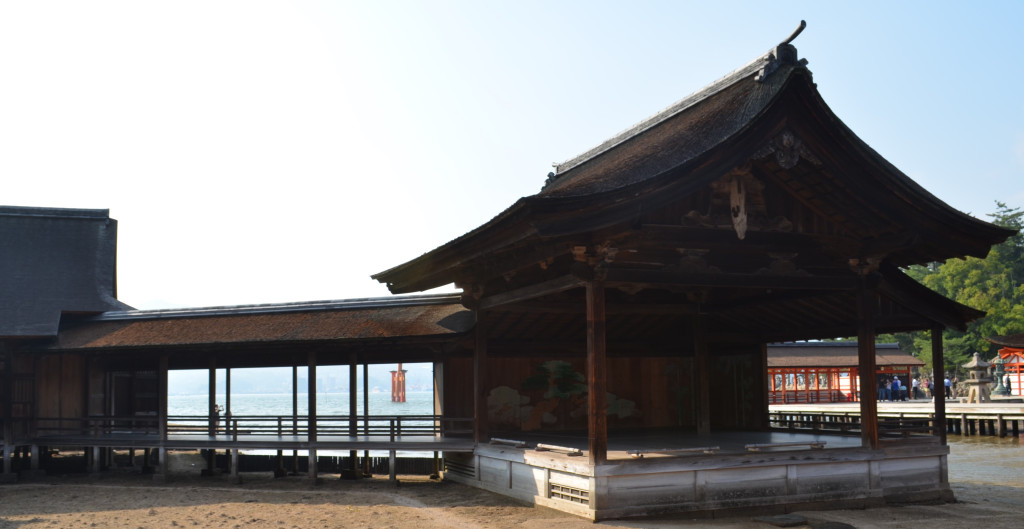 An old noh stage on a sandy beach at low tide.