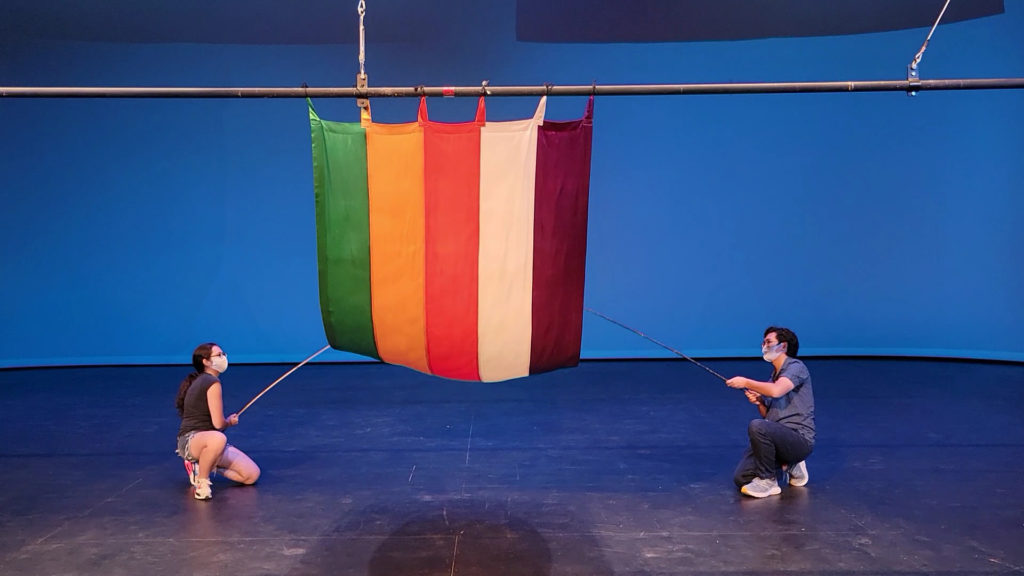 Two students use long, thin poles to pull up a green, yellow, red, white, and purple vertically striped curtain from the bottom.