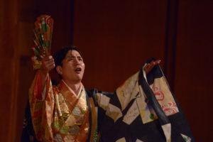 Shigeyama Sennojō III in an ornate kimono and outer robe holding a fanned looking upwards.