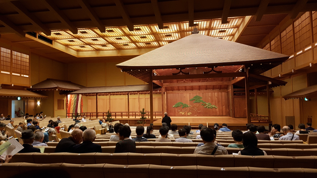 Wooden nogaku stage with theatre style seating to the front and the side of the stage