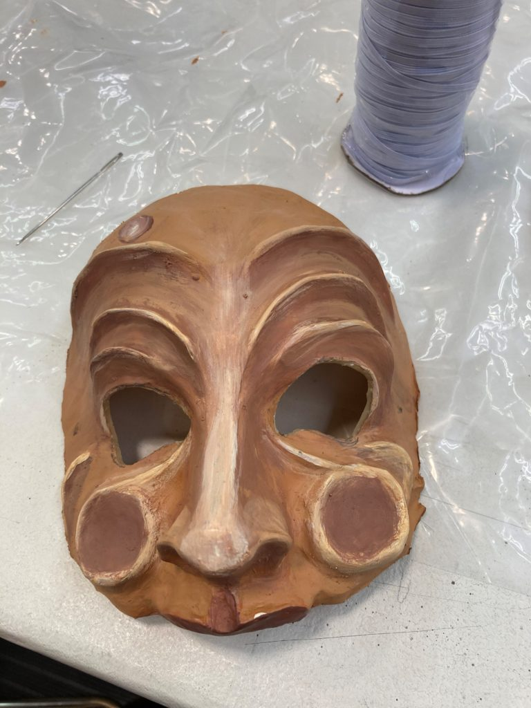 A half mask with exaggerated wrinkles above the eyes, circles on the cheeks and a bump in the forehead.