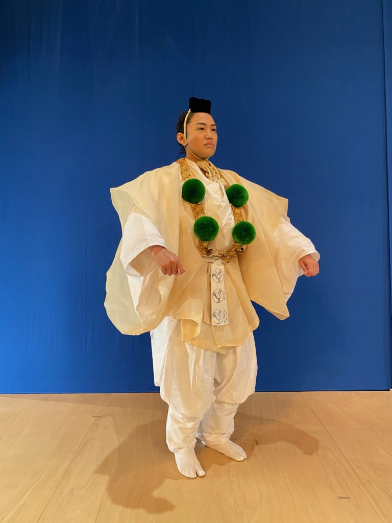 A woman in a white yamabushi's costume with green pompoms stands in front of a blue screen on a wooden floor