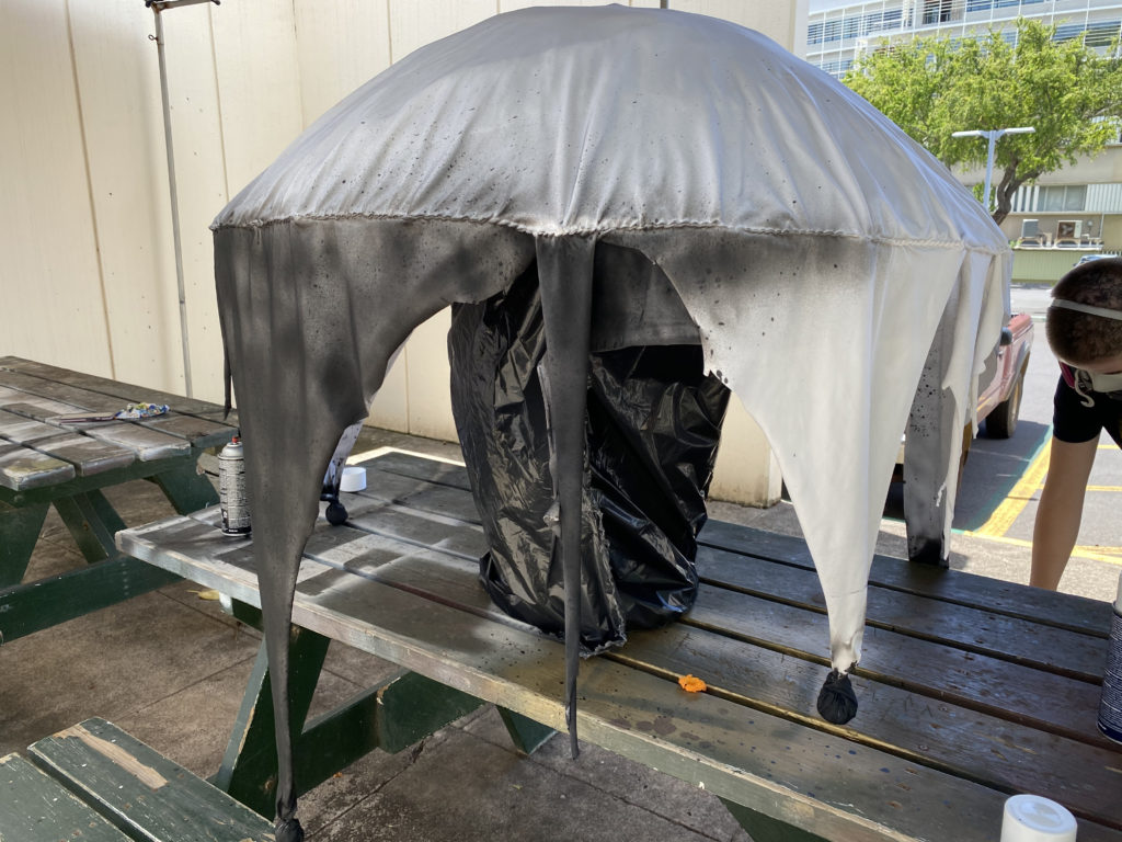 An umbrella with fabric strips hanging off of the rim sits on a stand, partially spray painted black.