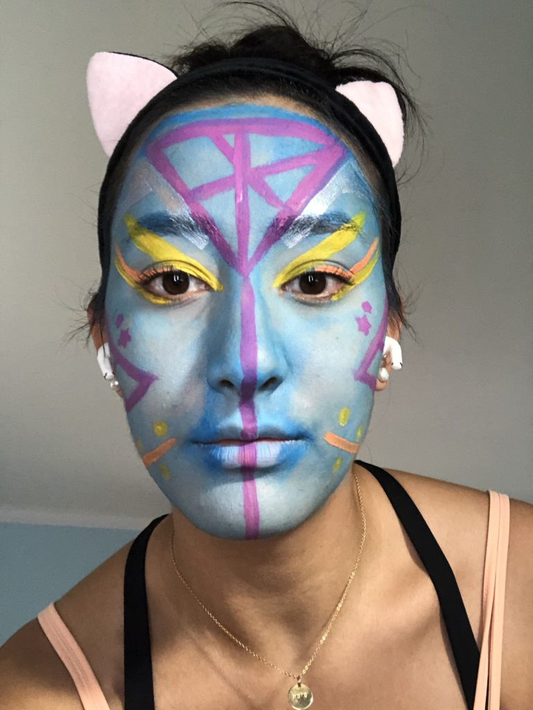 An actor in a cat ear headband has her face painted light blue with purple, orange, and yellow lines and geometric shapes on top.