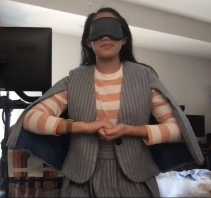 A woman in a orange and white striped shirt, a grey cape jacket and matching grey pants clasps her hands horizontally in front of her torso with a black sleeping mask over her eyes.