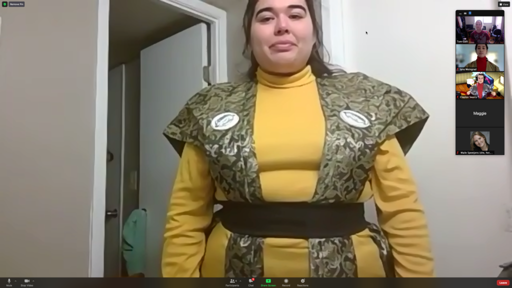 A screen shot of an actor wearing a yellow turtleneck with a green patterned kataginu over her shoulders and tied down around the waist with a black belt.