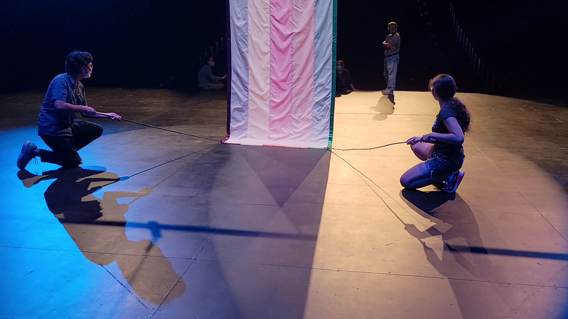 Two students hold long sticks tied to the bottom corners of the backside of a vertically striped curtain.