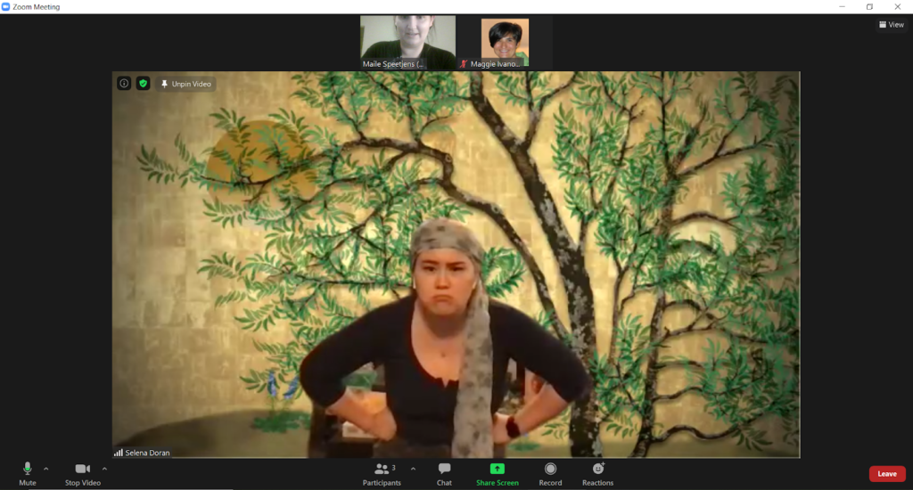 A Zoom screenshot of an actor in a black shirt with a grumpy face and a scarf tied around her head in front of a gold background with a pecan tree.