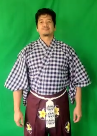 An actor stands in front of a green screen in a blue palaka kimono with a purple hakama with plumeria crests and a white koshi-obi.