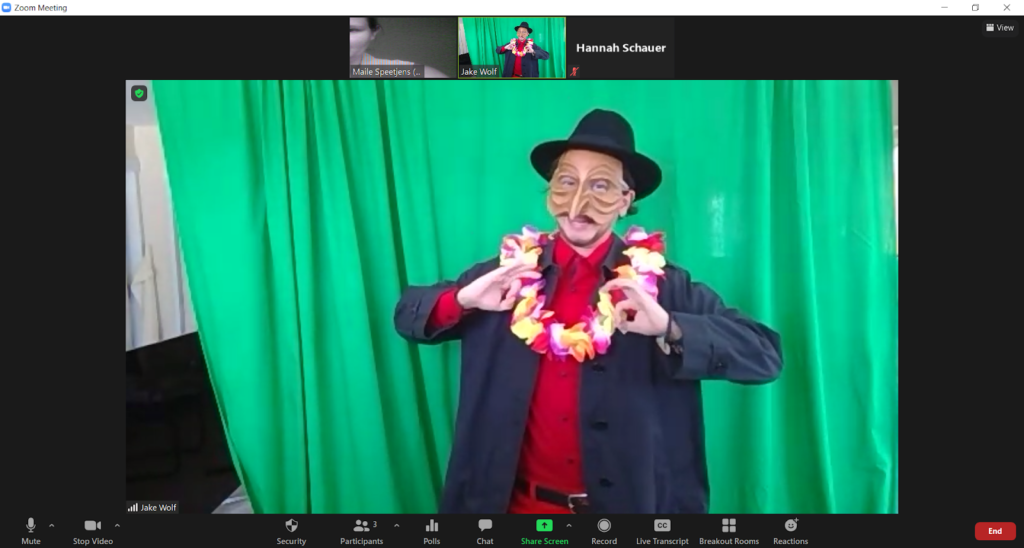 Screenshot of an actor posing in front of a green screen in a red collared shirt, black jacket, lei, black fedora and a pantalone commedia dell'arte mask.