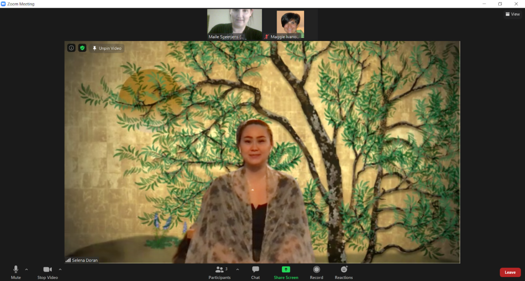 A screenshot of an actor sitting in front of a gold background with an illustration of a pecan tree wearing a black shirt with a translucent scarf draped over her shoulders.