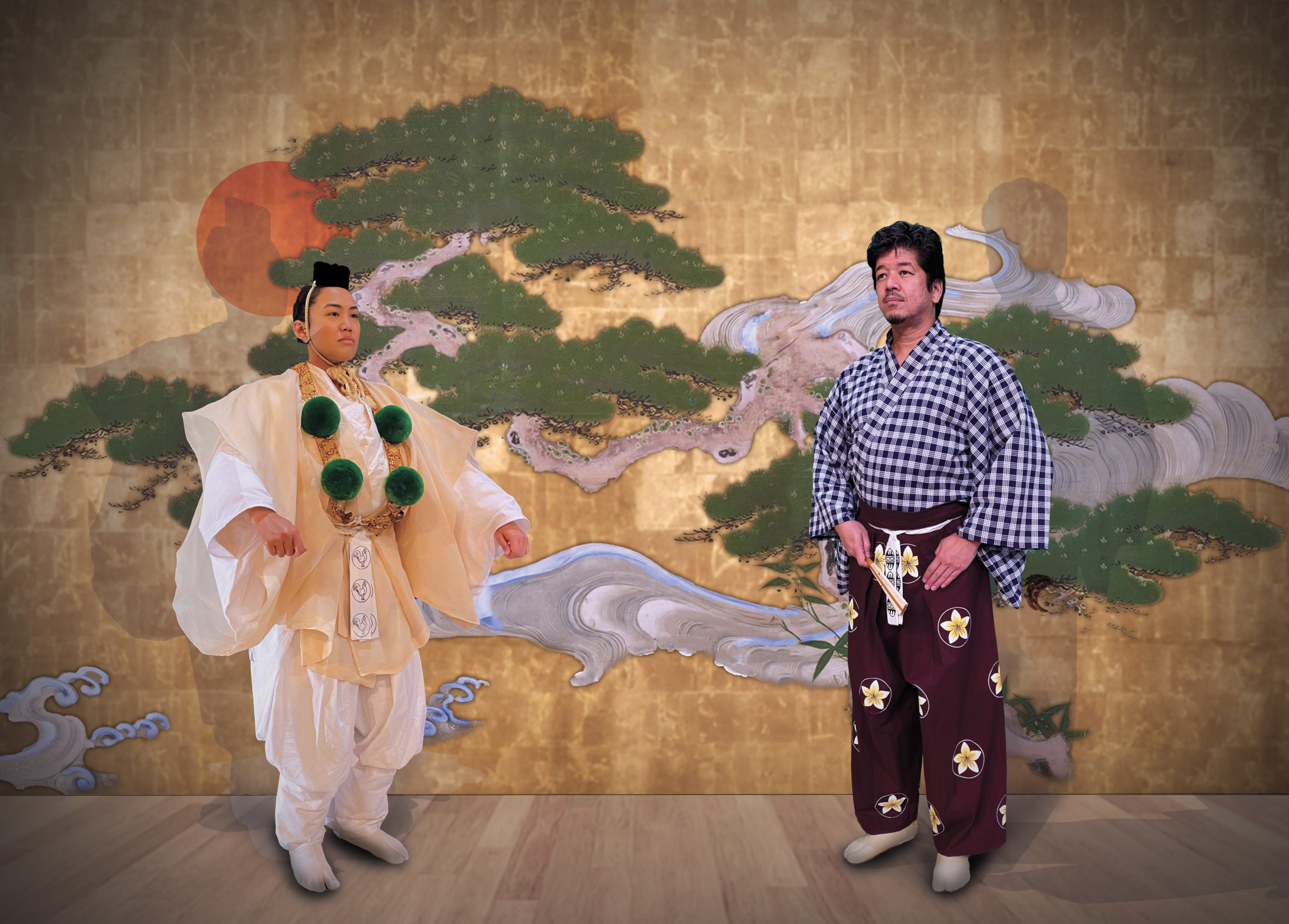 An actor in white yamabushi regalia with green pompoms and an actor with a blue palaka kimono top and plumeria patterned purple hakama stand in front of a pine tree backdrop on a wooden floor