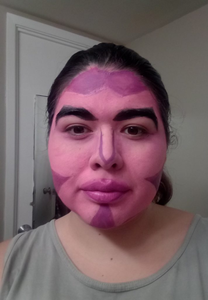 A woman with pink face paint accented at the edges with purple marks