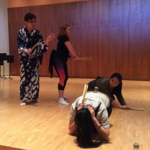 Shigeyama Sennojō III instructs a UHM student with a fan in hand while two more students duck on their hands and knees on the floor