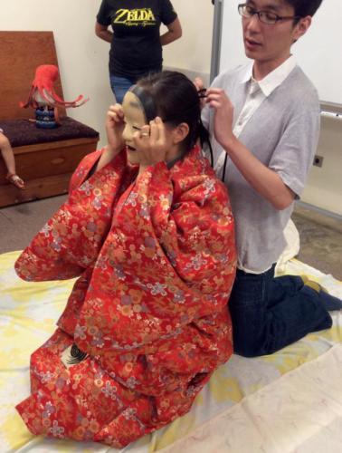 Shigeyama Sennojō III ties a noh mask onto a student in a red brocade kimono