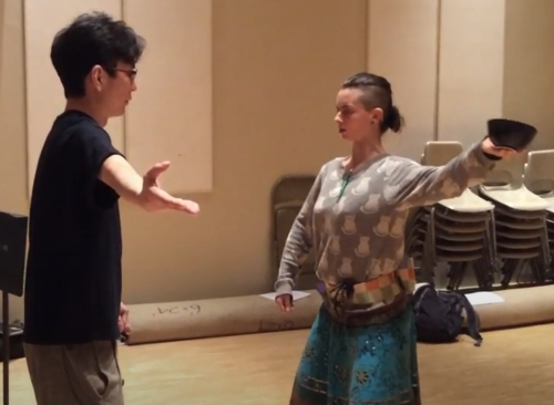 Shigeyama Sennojō III instructs a UHM student who mirrors him holding a bowl in an outstretched arm