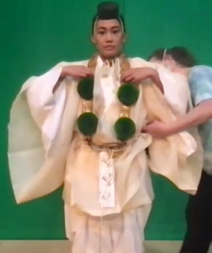 An actor stands in front of a green screen as a costume designer adjusts her white yamabushi kimono. She also wears green pompoms and a small, round, black hat.